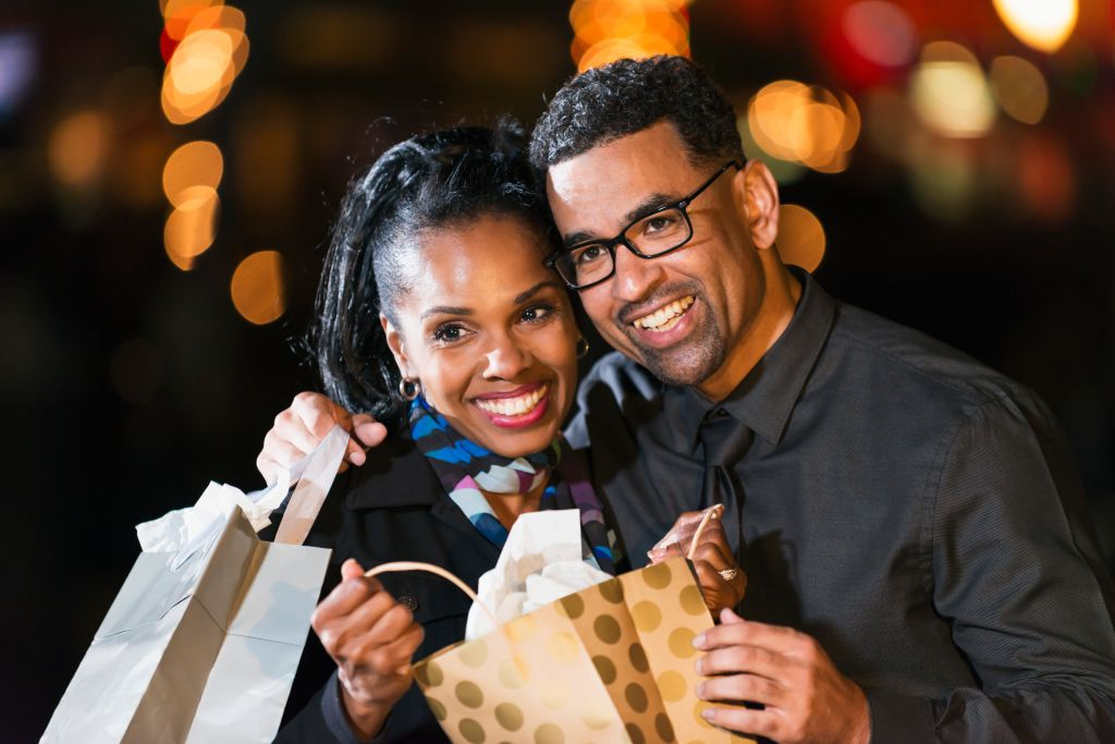Happy black couple opening a gift bag outdoors at night