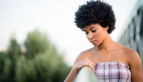 Sad teen girl standing on the bridge. Alone and thoughtful.