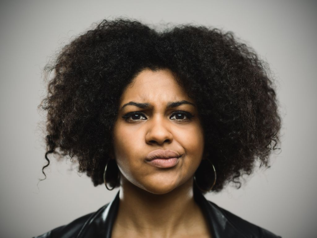 Close-up portrait of displeased young afro american woman