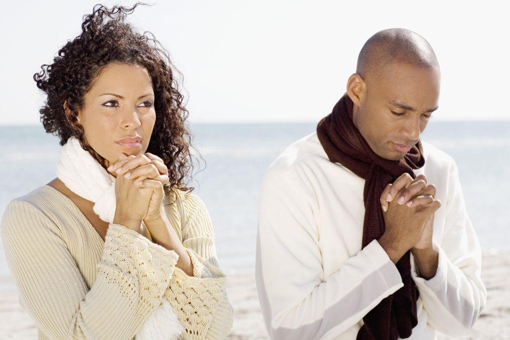 Couple meditating on the beach