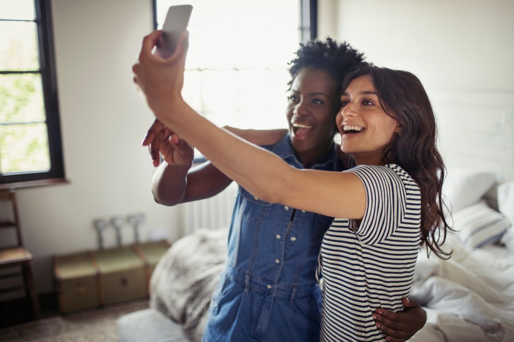 Smiling lesbian couple hugging, taking selfie with camera phone in bedroom