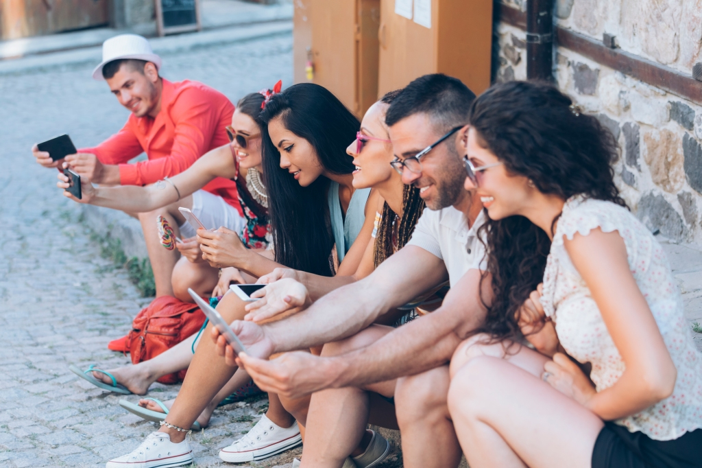Group of friends sitting on street and texting