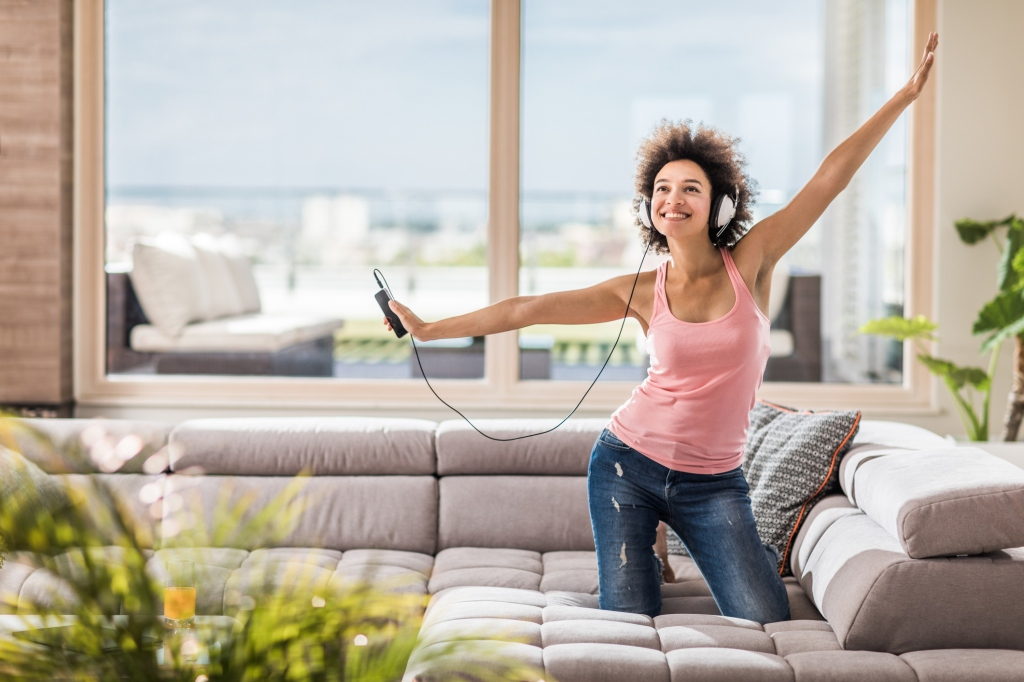 Carefree black woman enjoying in great music over MP3 player at home.