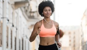 Young woman jogger running with headphones