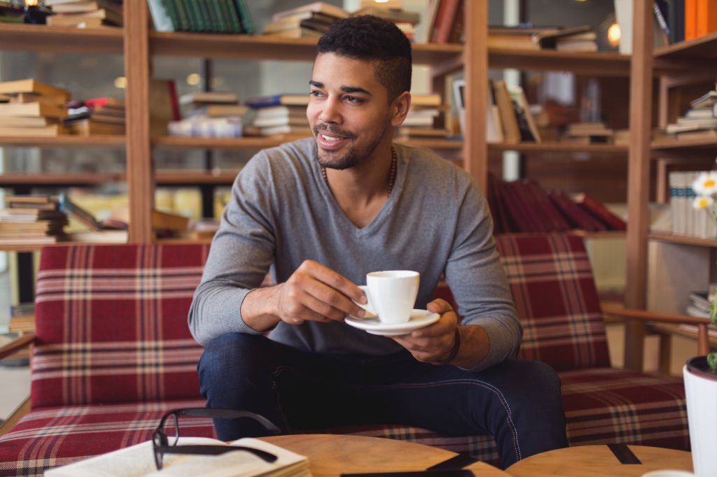University student enjoying coffee break while studying in library.