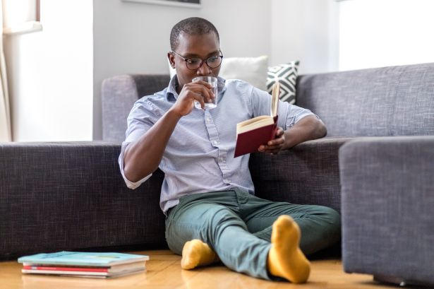Young man sitting on the floor in the living room reading book and drinking glass of water