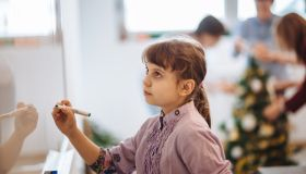 Little smiling schoolgirl writing on whiteboard