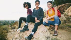 Portrait of smiling women sitting on rock