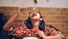 Tweenage girl eating noodles