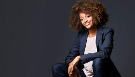 Businesswoman sitting against gray background