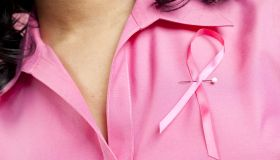 Woman wearing pink breast cancer ribbon on her blouse.