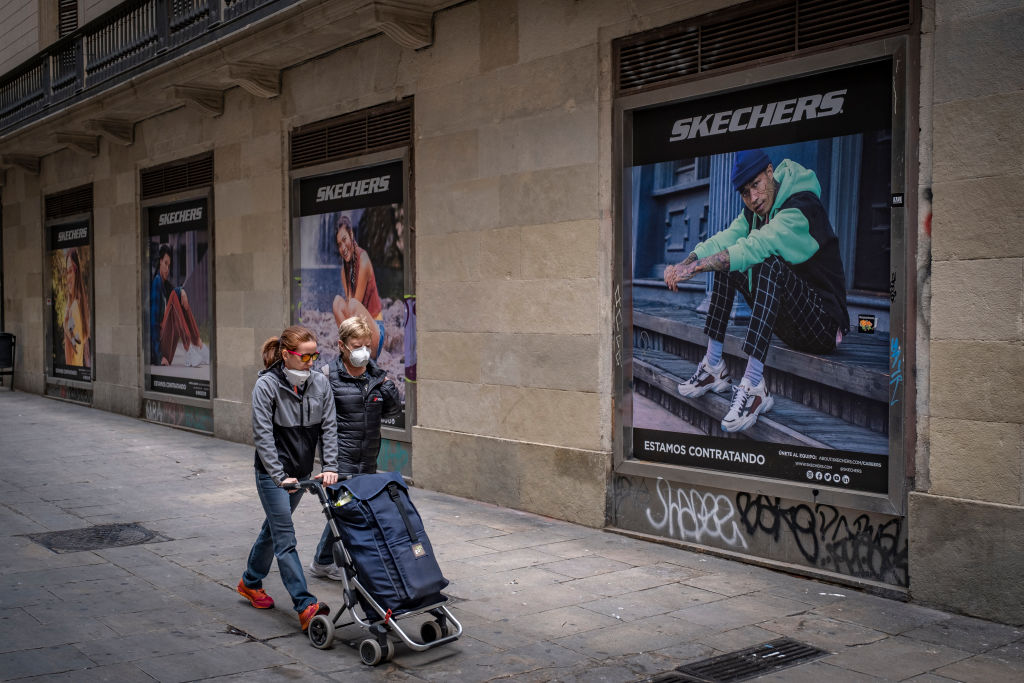 Women walking with a shopping cart along central shopping...