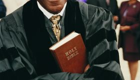 Portrait of a Smiling Priest Holding a Bible in His Crossed Arms With People in the Background