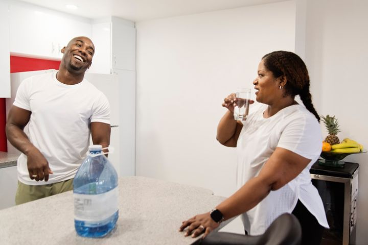 Mature adult couple drinking water doing exercise at home.