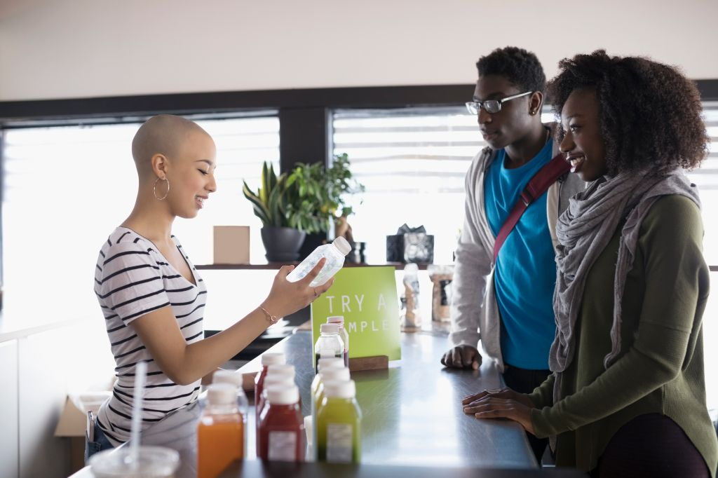 Teenage girl with shaved head working, helping customers at juice bar counter